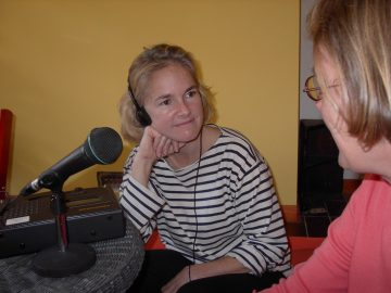 A women with head phones on listening to another women with a microphone in front of her